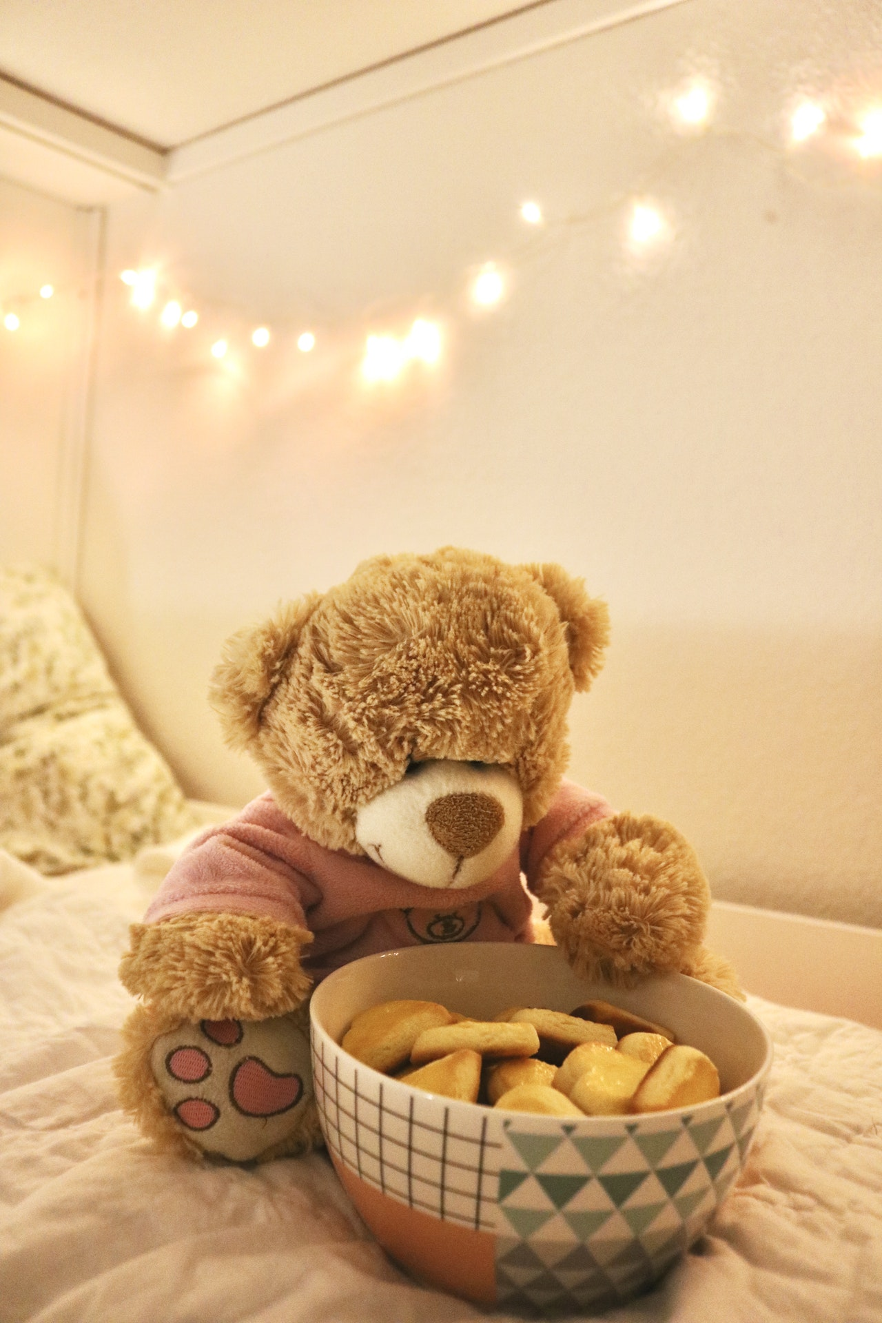 Teddy Bear On Bed With Lights On Wall