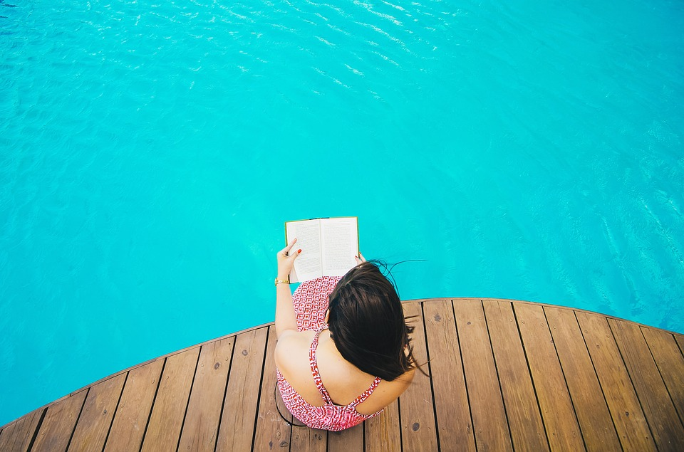 woman reading with her feet in a pool